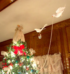 Doves decorating a Christmas tree with ornaments and beads